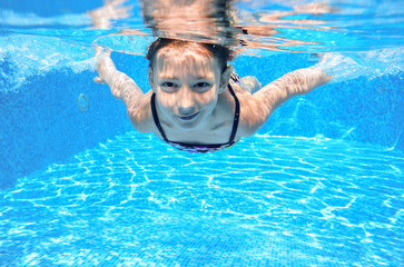Happy girl swims in pool underwater, active kid swimming