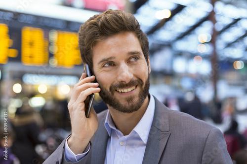 Leinwanddruck Bild Cheerful man on the mobile phone in hall station