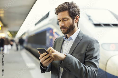 Man on platform station. Typing text message on mobile phone