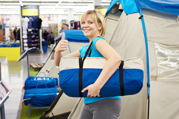 Happy woman chooses tent camp in store leisure goods