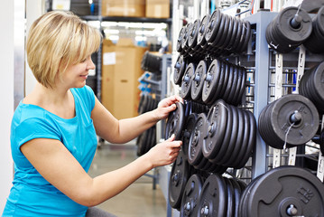 Happy woman chooses loads for dumbbell in sports shop
