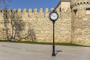 The clock on the background of the old fortress in Baku