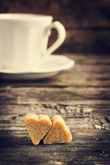 cup of coffe and brown cane sugar with shape of heart on old woo