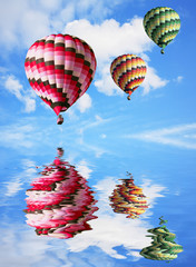 Three big balloons in the blue sky are reflected in water