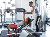 Fitness instructor  exercising with his client at the gym - 80959544