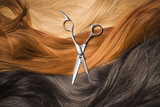 scissors on a background of dark red and blond hair