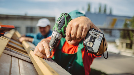 roofer using a drill is fastening a cap to a house roof