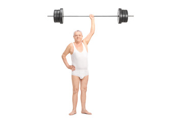 Semi-dressed senior lifting a heavy barbell