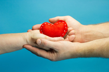 Red heart in woman and man hands on blue background