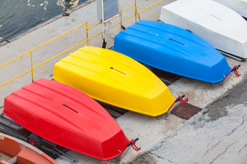Colorful plastic boats lay on the concrete pier