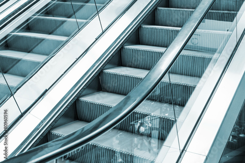 Foto op Aluminium Trappen Shining metal escalator moving up, blue toned