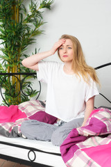 Blonde Frau sitzt im Bett und ist unentschlossen