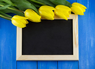Top view of yellow tulips with blank blackboard