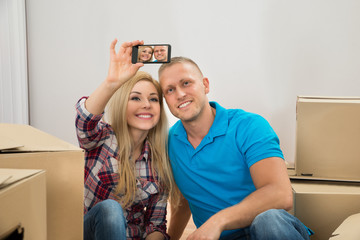 Young Couple Taking Selfie In Their New House