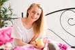 Blondes Mädchen geniesst einen Kaffee im Bett