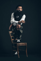 Bearded Guy Looking Afar with One Foot on Chair
