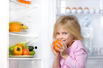 Little girl holding orange near open fridge