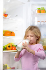 Little cute girl drinking milk near open fridge