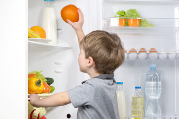 Little cute boy picking orange from fridge