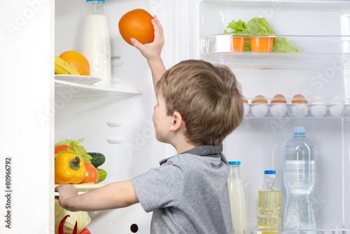 Little cute boy picking orange from fridge - 80966792