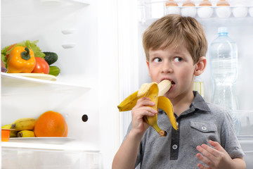 Cute boy eating banana near open fridge