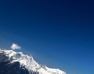 Verscheintes Hochgebirge mit kleiner Wolke