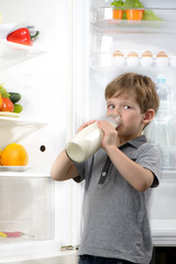 Funny little boy drinking milk near open fridge