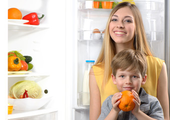 Young mother and her little son near open fridge