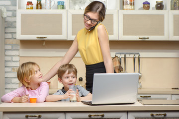 Young business woman in kitchen with her little children