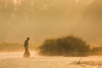 Reflection: man rowing on the boat in the foggy