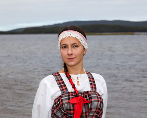 Young girl in national dress at the river shore