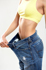 Diet. Beautiful Sporty Woman Showing How Much Weight She Lost. H
