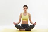 Fototapety Yoga. Woman Meditating and Doing Yoga Against White background