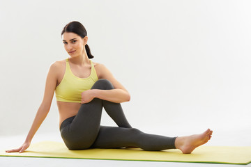 Woman doing stretching exercises against white