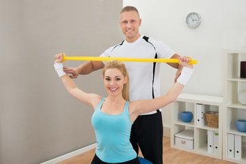 Instructor Standing Behind Woman Exercising