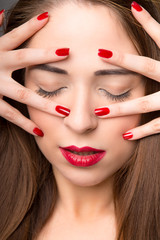 Portrait of attractive young female with red nail polish, on dar