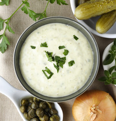 Tartar sauce in a bowl with ingedients.