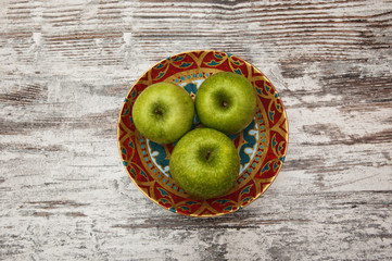 Green apples on a beautiful plate