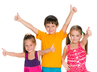 Three cheerful children hold their thumbs up