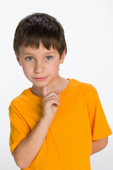 Thoughtful little boy in a yellow shirt