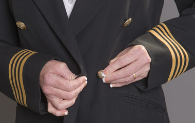 Airline officer fastening button on her uniform