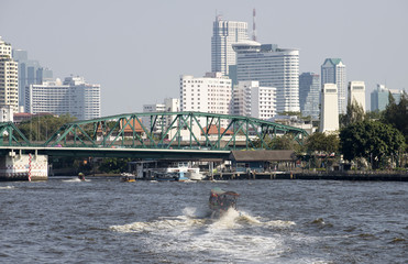 A longtail water taxi approaching Memorial Bridge Bangkok