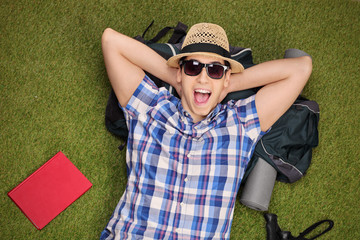 Excited male hiker lying on his backpack in a field