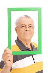 Happy senior posing behind a green picture frame