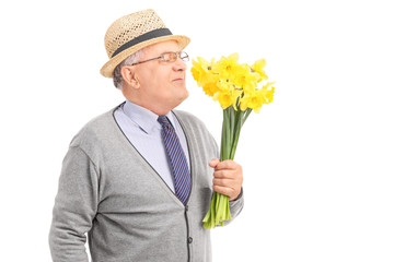 Senior gentleman smelling a bunch of yellow tulips