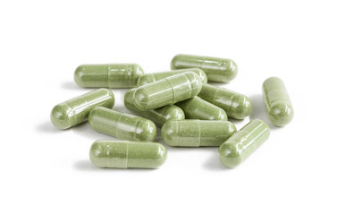 Capsules of green herbal supplement product isolated on white ba