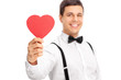 Young guy holding a heart shaped piece of cardboard