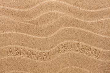 Abu Dhabi  inscription on the wavy sand