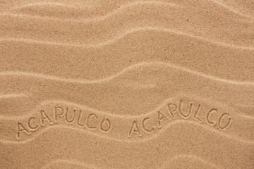 Acapulco  inscription on the wavy sand