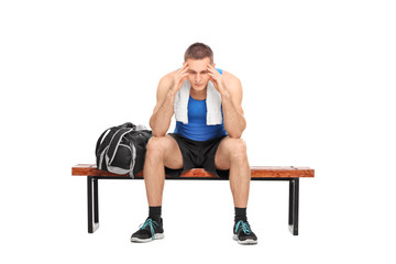 Worried athlete sitting on a bench